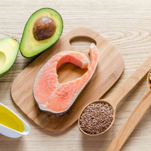 avocado, salmon, walnuts and seeds on a wooden spoon