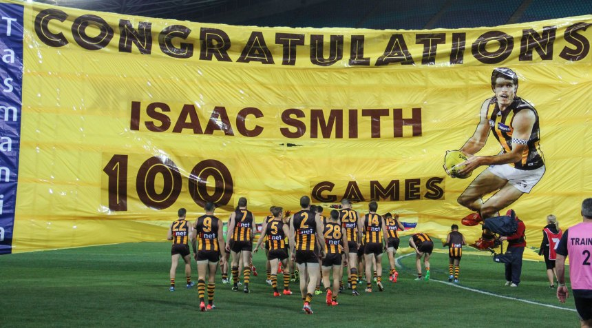 The Hawthorn Football club head out onto Homebush Stadium via the Isaac Smith 100th game banner