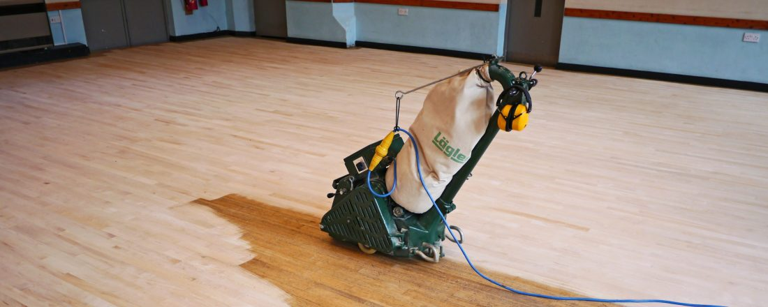 Professional dustless Lagler Hummel belt floor sanding machine on large maple floor