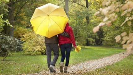 Couple walking on path in New England on rainy day. This image represents how to fall in love again after attending a Hold Me Tight in Massachusetts or a private marriage retreat in Massachusetts.