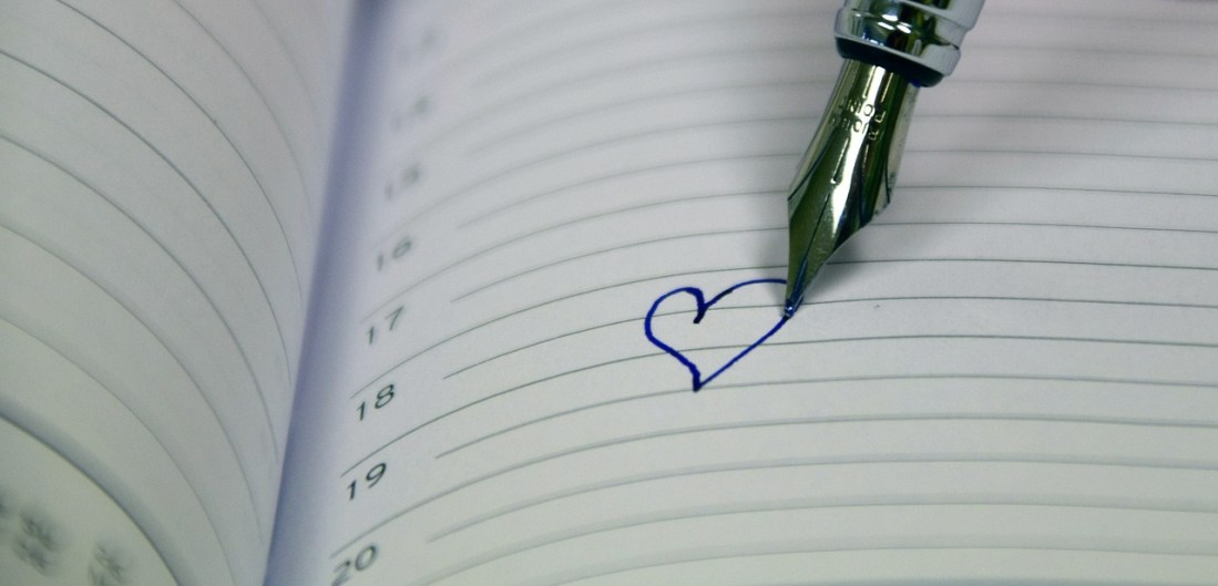 Pen writing heart into a book. This image is meant to portray participating in a marriage retreat for lesbian couples or lesbian-friendly couples therapy retreats.