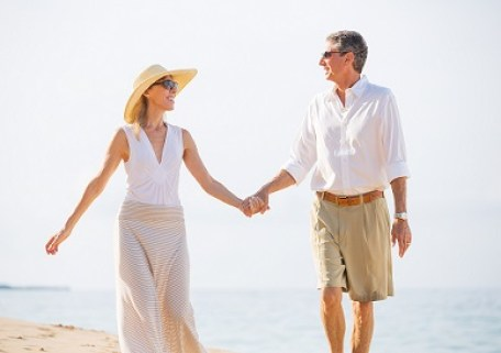 Empty Nesters walking on the beach holding hands. Image is meant to represent married couple falling in love, feeling emotionally connected with mutual appreciation.