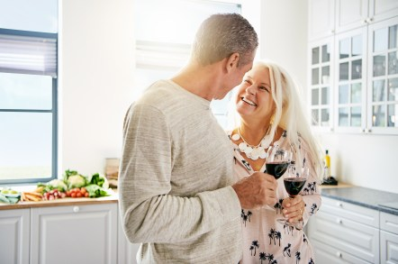 Empty nest couple smiling with contentment in a white kitchen. This image is meant to portray good communication and connection that occurs from attending a couples retreat in Maine or a couples retreat in Connecticut.