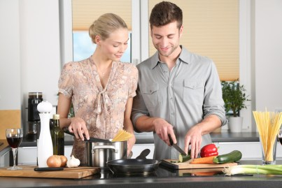 Couple smiling and cooking in kitchen. This image is meant to portray emotional connection that can happen after attending a marriage seminar in New England or a marriage retreat in New England.