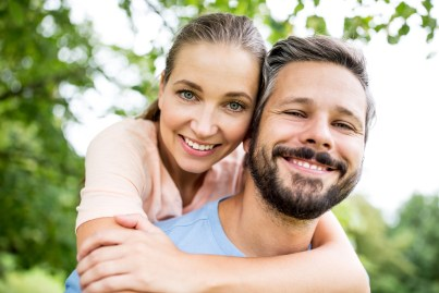 Couple hugging each other with both facing forward towards the camera. This image is meant to portray improved communication skills that occur from couples attending Emotionally Focused Intensive Couples Therapy in New England.
