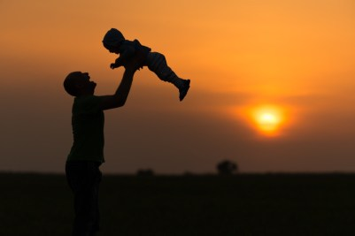 Parent lifting up child with sunset in background. This image is meant to portray feeling emotionally connected after attending a Hold Me Tight Workshop in New England or a Hold Me Tight Workshop in Massachusetts.