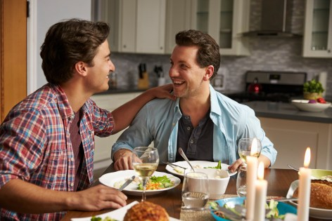 Bi-racial male gay couple connecting over meal. Image is meant to portray LGBTQ couples feeling emotionally connected after attending a couples retreat in Maine, a couples retreat in Massachusetts, or a couples retreat in Connecticut.