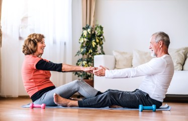 Empty nest couple smiling at each other as they exercise together. This image is meant to represent the emotional connection a couple obtains after attending a couples therapy retreat in Maine or a couples therapy retreat in Massachusetts.