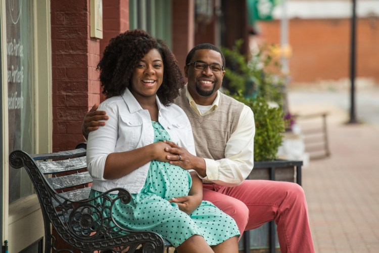 Pregnant African American woman sitting with her husband on a bench. This image is meant to portray improved communication from marriage counseling retreats in New England.
