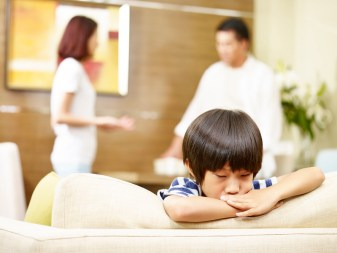 Asian child unhappy with parents arguing in background. This image is meant to portray emotional disconnection and the need to attend a couples therapy retreat in Connecticut.