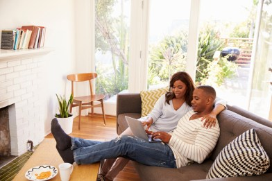 Black couple Relaxing On Sofa At Home Using Laptop. Signifies good communication after attending intensive marriage counseling in Connecticut with emotionally focused therapy.