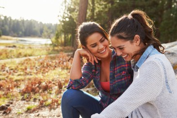 Happy lesbian couple laughing together in the countryside. Signifies feeling hope about attending lesbian couples retreats in 2020 and having a lesbian relationship coach or a lesbian expert..