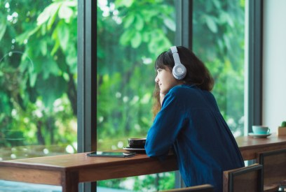 Possibly LGBT woman listening music with headphones near window at cafe.  Feeling peaceful after attending a hold me tight couples workshop in Massachusetts.