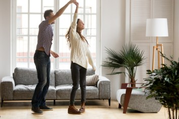 Couple dancing in living room. Signifies good communication and less conflicts after attending marriage seminar New England or marriage retreat New England.