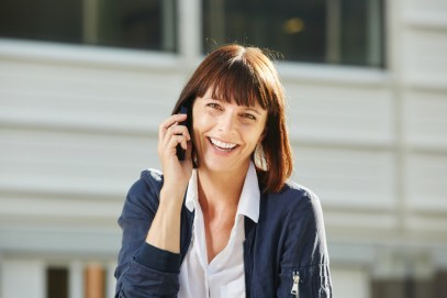 Laughing woman talking on smart phone outside. Signifies feeling hope about attending an emotionally focused therapy intensive or intensive marriage counseling with emotionally focused therapy.