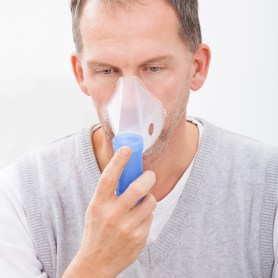 Man inhaling from oxygen mask. Signifies the need for couples retreat Massachusetts.