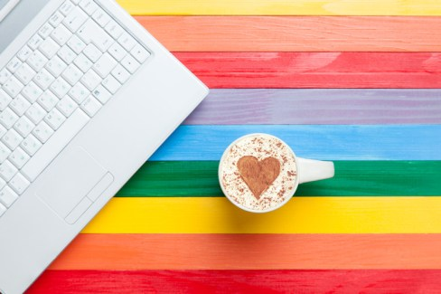 Rainbow colored table with laptop and cappuccino signifying a marriage retreat for lesbian couples or an online LGBT couples workshop and lesbian friendly ONLINE Hold Me Tight Workshop for lesbian couples.