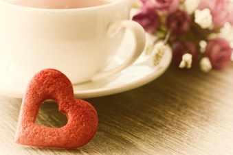 Coffee with heart cookie and flowers on table. This signifies better communication for couples through attending couples retreat in Massachusetts or couples therapy retreats in Massachusetts.