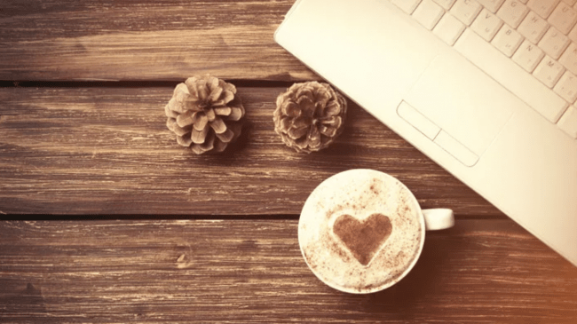 Keyboard with cappuccino and pine cones on wooden table. This is signifying couples relationship help during COVID with ONLINE couples workshop and the HOLD ME TIGHT program for couples.