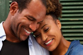Close up portrait of cheerful couple in love smiling on green background. This signifies an emotional connection and better communication skills and better relationship due to a private couples retreat.