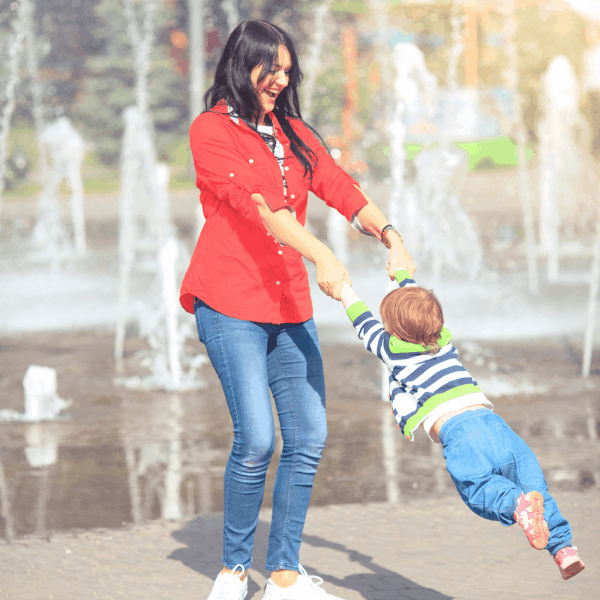 mom swinging her child by the arms near a water fountain having fun in the summer