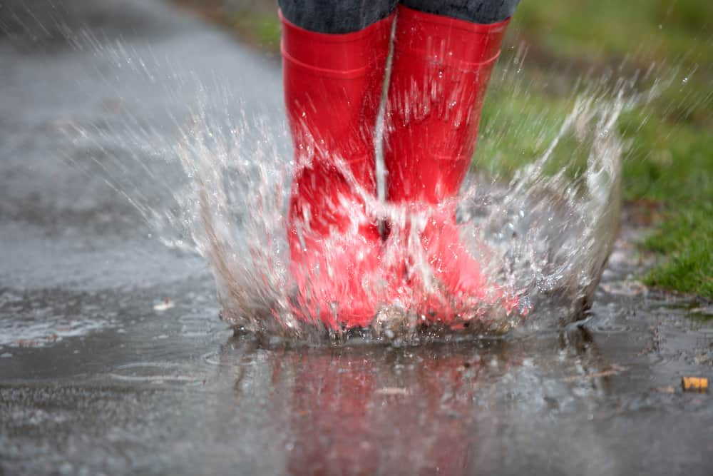 Child's red boots splashing in the rain puddles while camping
