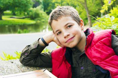 teenage boy smiling in red vest