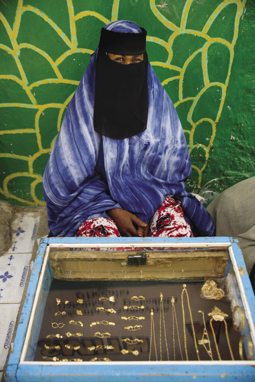 Awoman selling gold from a stall in Hargeisa market sits behind a display case.