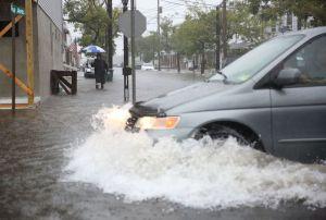 Van driving through flooded community