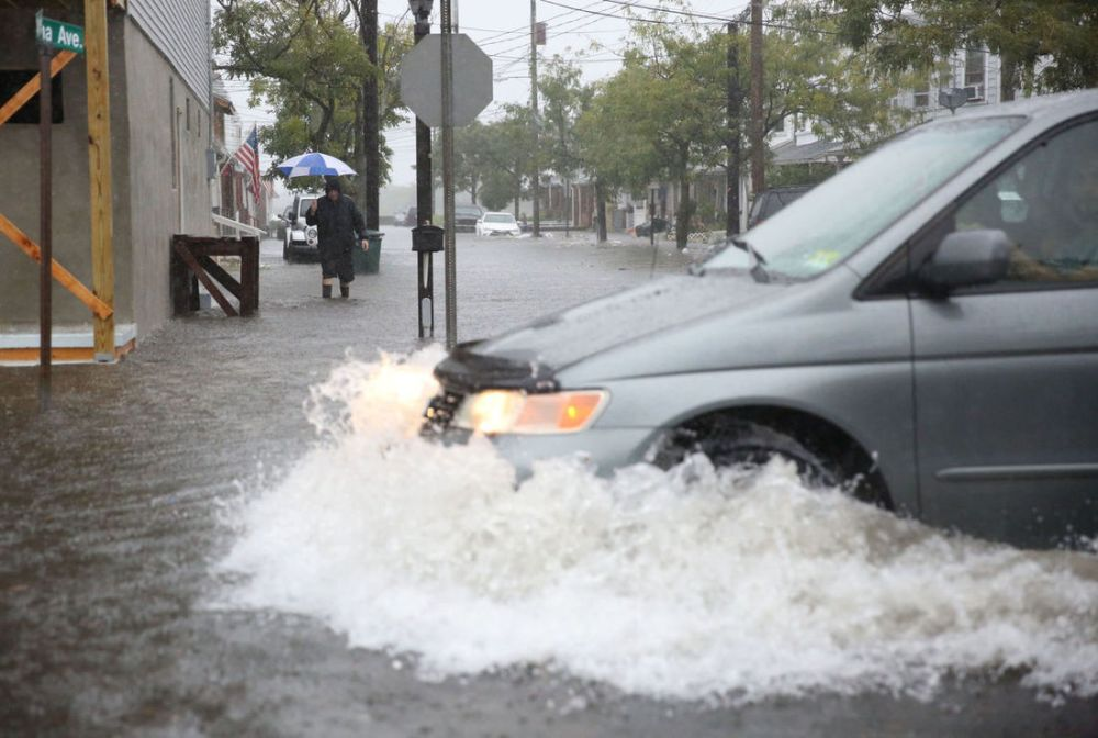 Van driving through flooded street