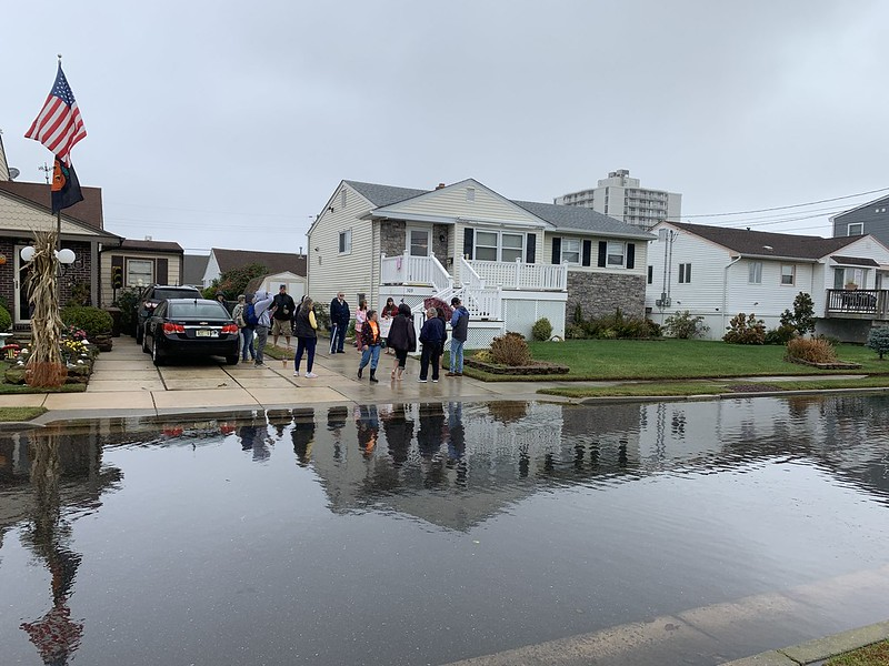 New Jersey Organizing Project members stand on a flooded street