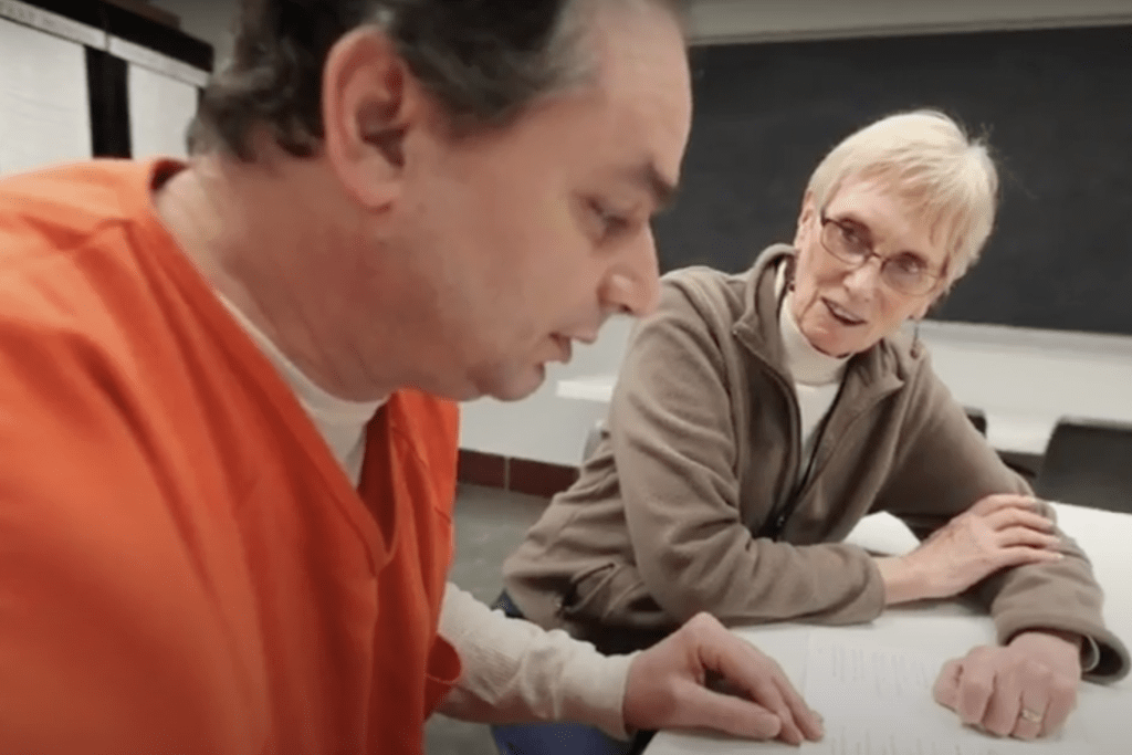 Woman sitting with an inmate and looking at text on a paper