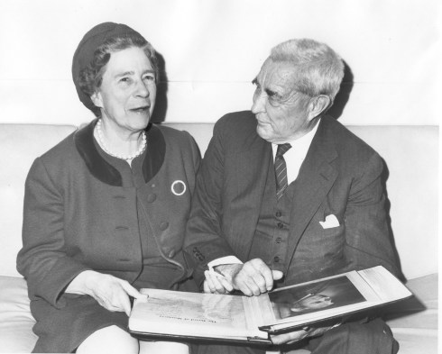 Black and white photograph of an older couple, seated next to one another with a scrapbook on their laps.