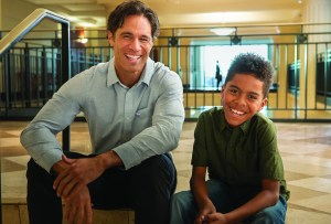 Image of CASA volunteer and young boy smiling in courthouse