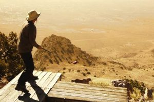 Golfer stands on platform on top of Socorro's M Mountain ready to hit shot
