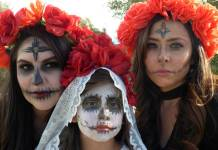 Three women celebrating Day of the Dead