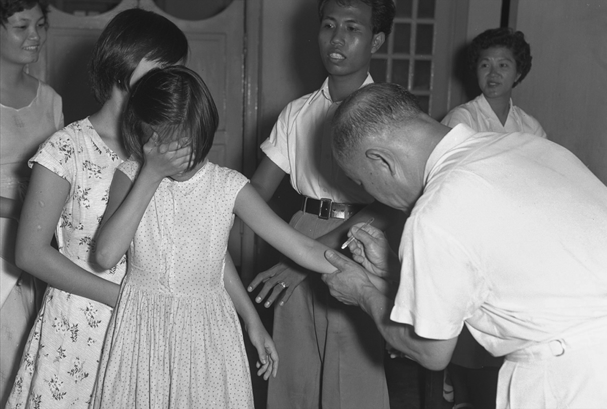A girl covering her face as she is being vaccinated for smallpox on 16 April 1959.