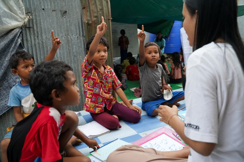 Young children study the Khmer alphabet during an afternoon class led by a student teacher.