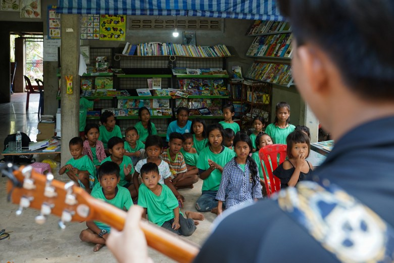 A youth volunteer from Siem Reap City plays guitar for students at the Village Library in Areak Svay Village after learning about the project on social media.