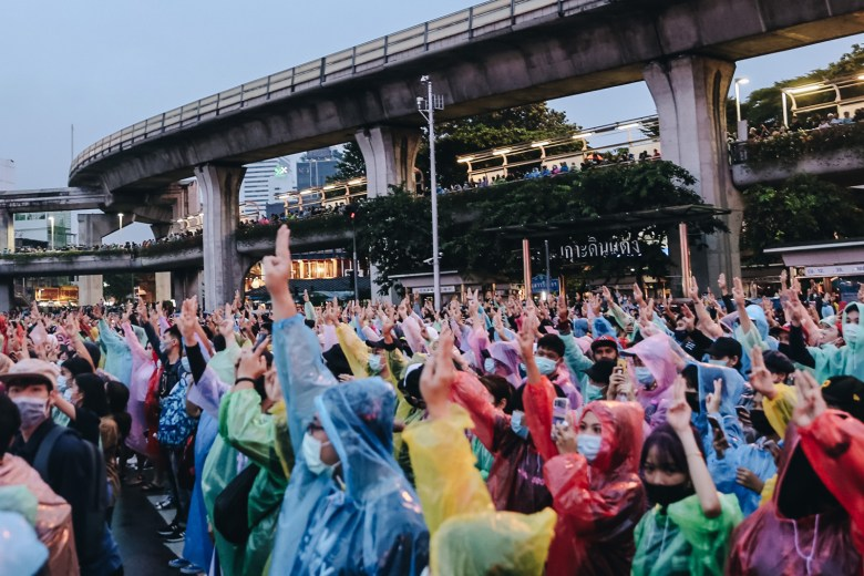 Protestors donning rain jackets raise the movement's signature three-finger salute during a rally at Victory Monument in Bangkok on 18 October 2020.