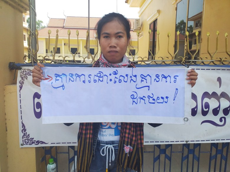 """Mother Nature Cambodia activist Long Kunthea protests the arrest of environmental activist Ouch Leng in Stung Treng province in March 2020, holding a sign reading: """"No release, no withdrawal."""""""