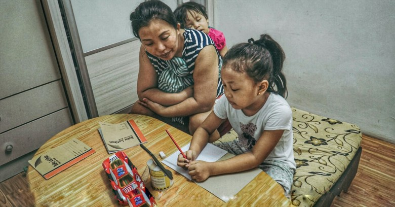 A Chin refugee mother from Myanmar studies at home with her daughter in May 2020 while the girl's learning centre in Kuala Lumpur was closed due to the coronavirus pandemic.