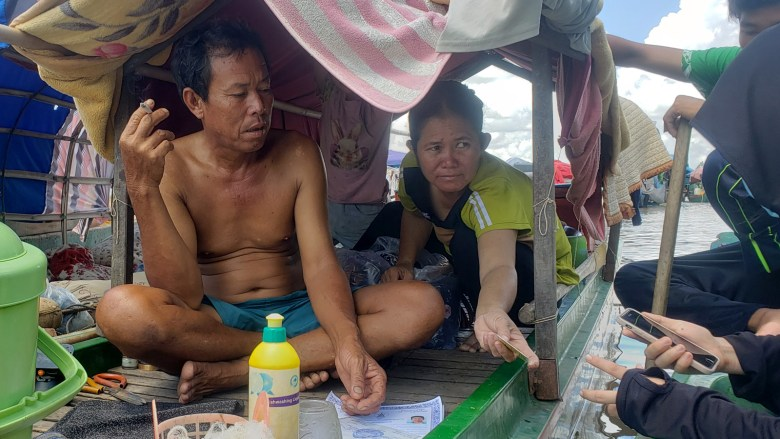 An ethnic Vietnamese couple aboard their fishing boat on the Mekong River near the Cambodia-Vietnam border show reporters their IDs and other documents in July 2021.