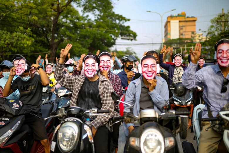 Protesters in Mandalay, Myanmar, raise the anti-coup three-finger salute while holding up Dr. Sasa face masks on 22 May 2021.