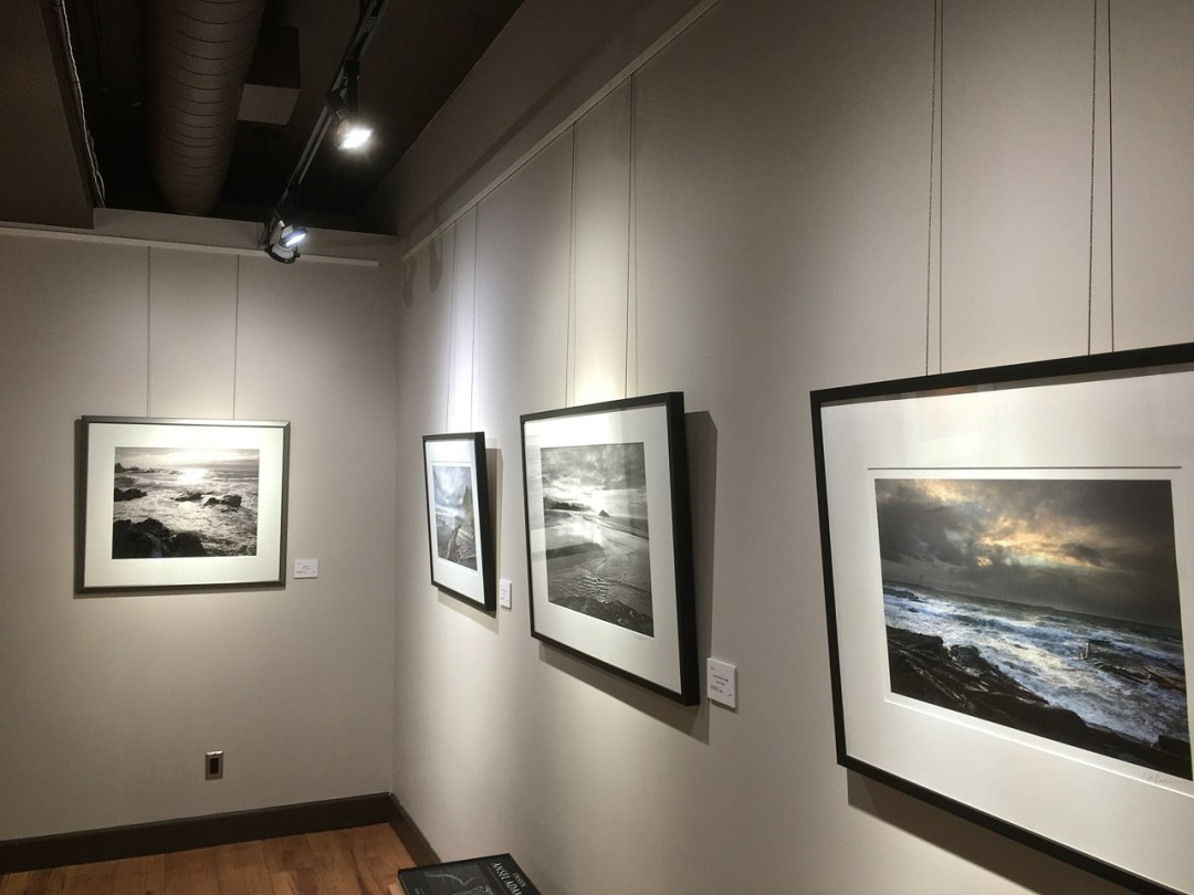 View of corner of gallery with several prints hanging on both walls.