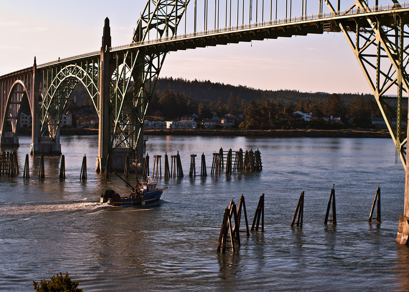 A fishing vessel heads out to sea under the Yaquina Bay Bridge