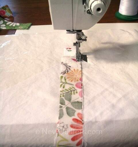 Photo of fabric strip being sewn onto string quilt block