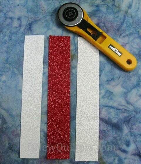 Photo of three fabric strips with rotary cutter