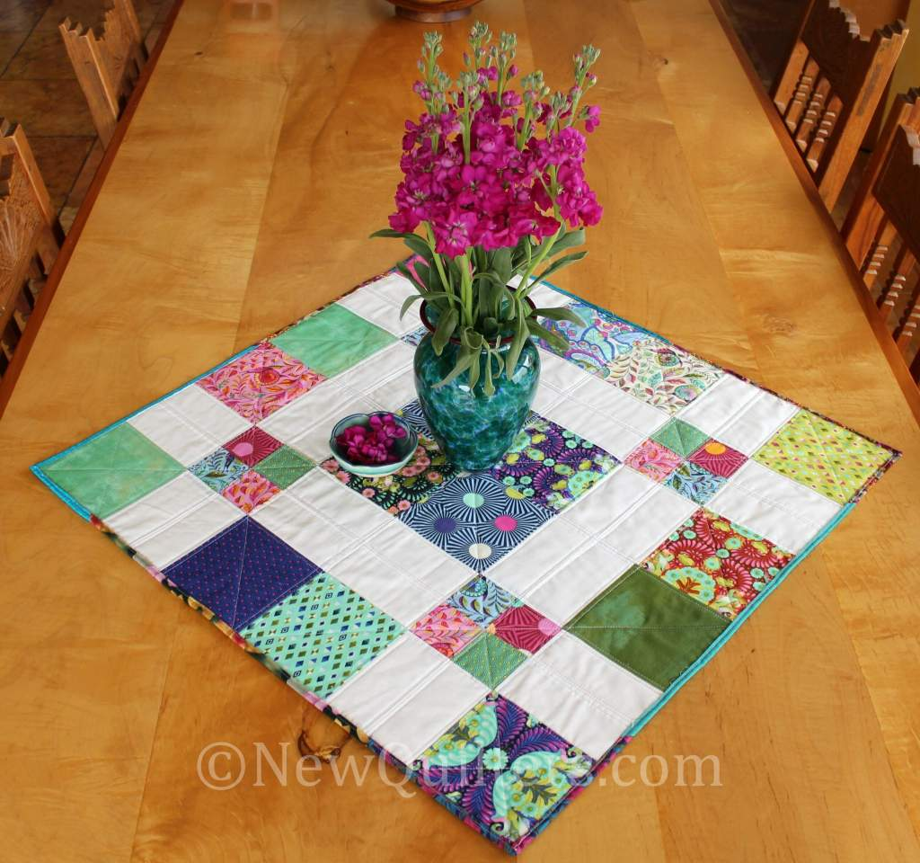 Photo showing finished disappearing 9-patch table topper quilt