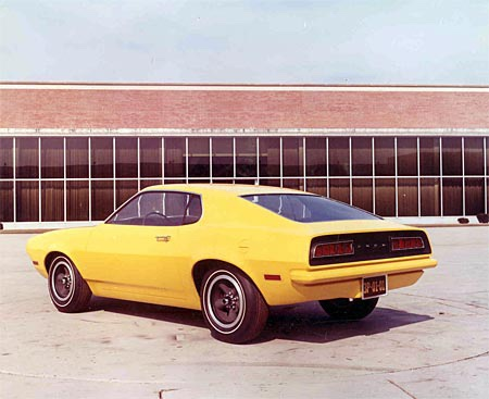 Yellow Ford Pinto in front of industrial building